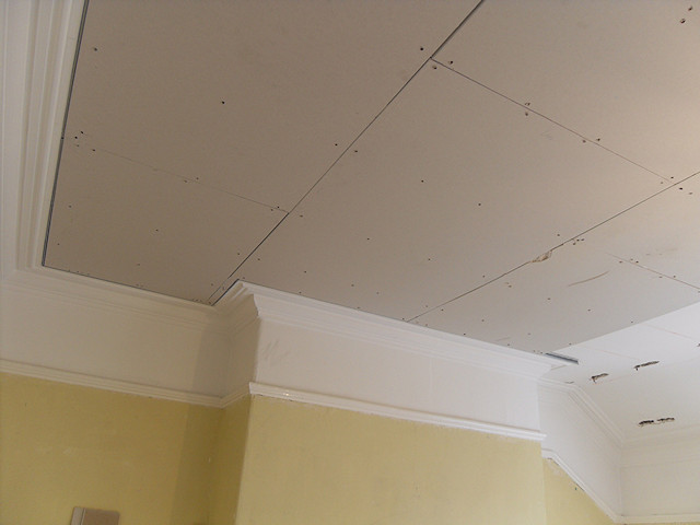 Overboarding of ceiling to protect sensitive corniche