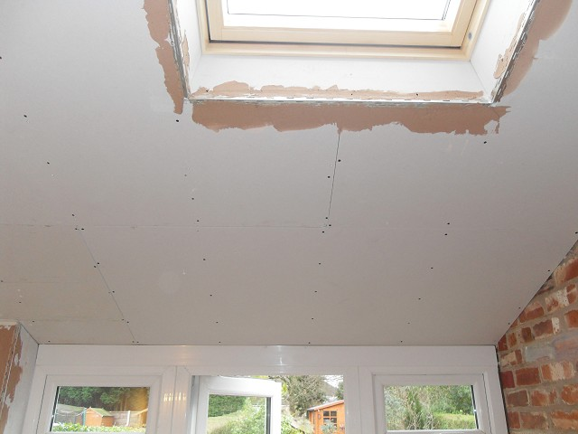 Plasterboard ceiling built-up around joists and Velux.