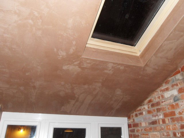 Finished plaster ceiling and feature brick wall.