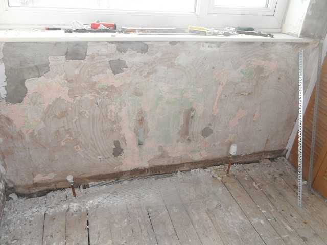 Beneath the window, showing the poor condition of the plaster in this room.